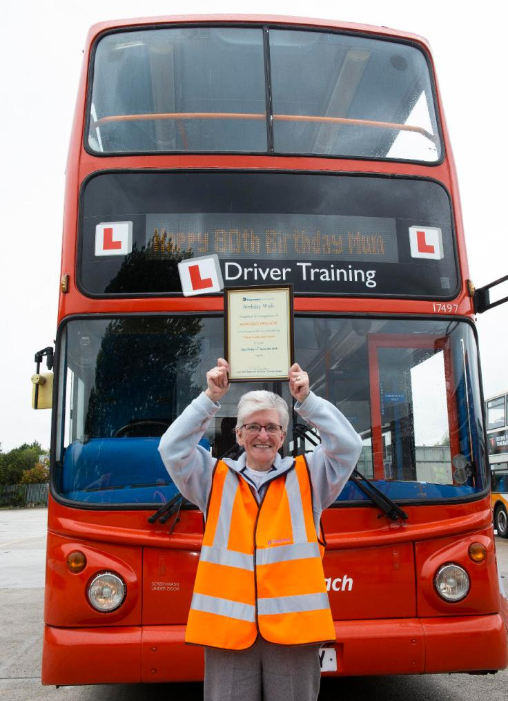 A happy Margaret Swallow, holding her Driving Experience certificate.