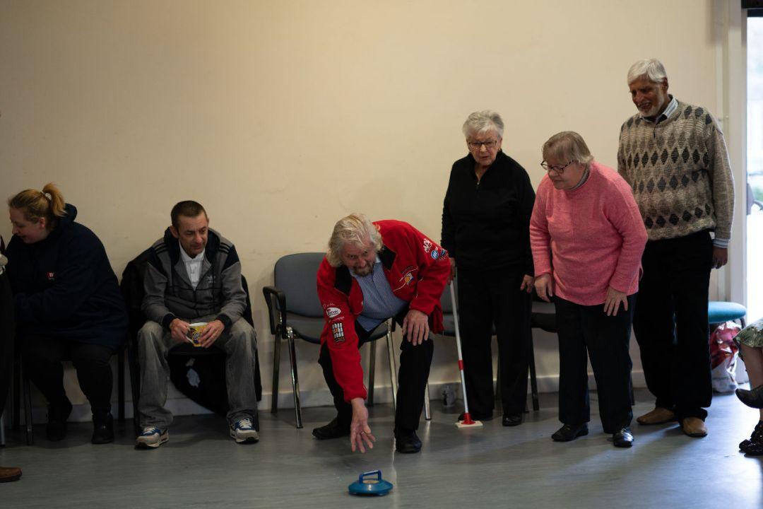 Elderly people playing indoor curling